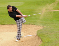 a male golfer swings his club pivoting on one leg to drive the ball out of a bunker