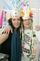 A young person with a brightly coloured feather headress standing next to a laday with her arm around them smiling.