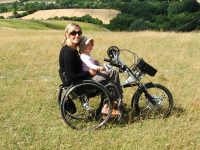 Kristina wearing sunglasses on a beautiful sunny day, sat in a wheelchair with Bike adaption in the middle of green fields with a young child sat on her lap.