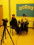 two young people, one is a wheelchair user, are sat smiling facing a camera on a tripod with the word DANCE on the wall behind them
