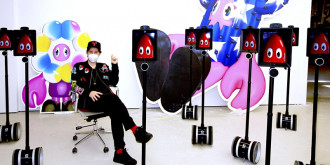 Philip Colbert sitting down and wearing a mask in front of his exhibition 'Lobsteropolis