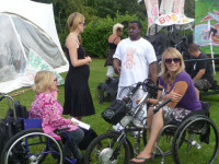 Two young women who are wheelchair user's sitting outside on the grass with tent like structures behind