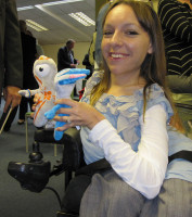 A photograph of Esther Apleyard holding both the Mascots for the Olympic and Paralympic Games.  They are soft toys, about 15cms heigh mainly in blue and white and orange and white.  They have helmet type shapes on their heads and one central eye which represents a camera